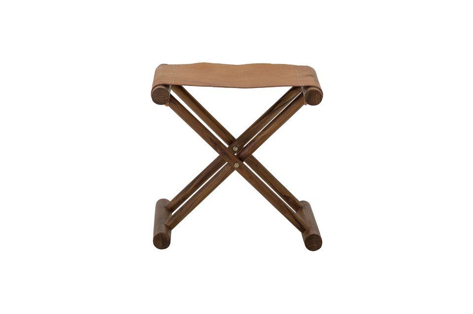 Seine gekreuzten Beine bestehen aus dunkelbraun gebeiztem Teakholz, der Sitz ist aus Naturleder